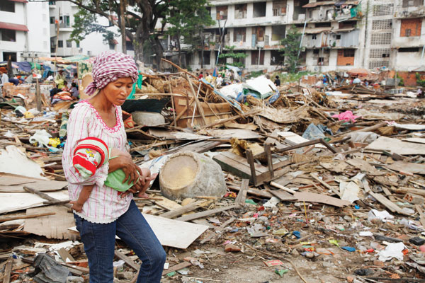 Former Borei Keila resident Yim Mady, 42, carries her child past debris from homes demolished by local authorities
