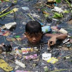 2A29C5B700000578-3148193-Scavenging_A_boy_sift_through_floating_garbage_as_he_collect_rec-a-12_1435912665073